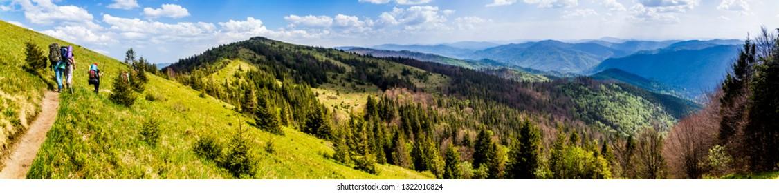 group of tourists hiking in carpathian mountains, national park Skolevski beskidy, Lviv region of Western Ukraine