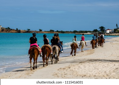 Group of tourists horseback riding on the beach in Antigua Island,  Day at the beach in St.John, Antigua & Barbuda Island, Caribbean.