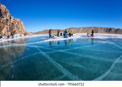 group of tourists with ice sleds walking along the ice of Lake Baikal.