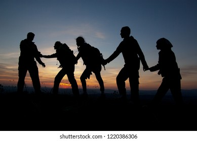 A group of tourists on top of a mountain at sunset.
