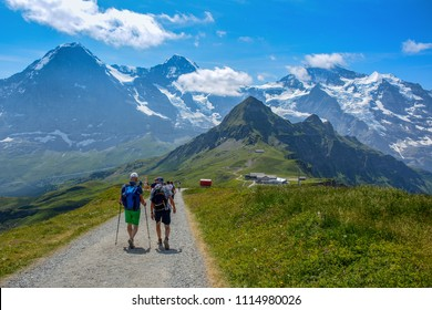 A group of tourists with the panoramic view of the Swiss Alps with the famous peaks including Jungfrau, Monch, Eiger and Mannlichen cable car station, Grindelwald, Bernese Oberland, Switzerland.