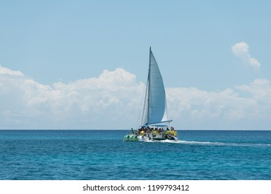 Group of tourists relaxing on catamaran during adventure trip to Saona island in Caribbean sea