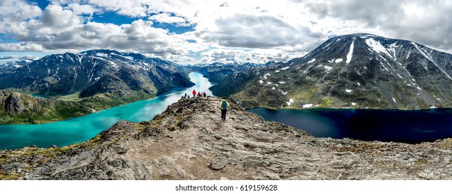 a group of tourists traveling mountains passing between two lakes of different colors. Jotunheimen Norwey