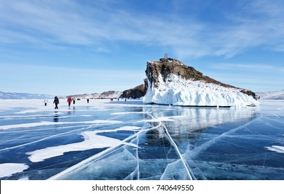 A group of tourists travels along the ice of the frozen Lake Baikal. Excursion to the beautiful iced rocks of Horin-Irgi or Cape Kobyliya Golova