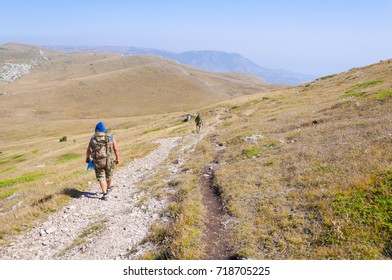 A group of tourists travels along the mountain trails in the Crimea. The Chatyr-Dag mountain, autumn. On a background of yellow grass and blue sky.