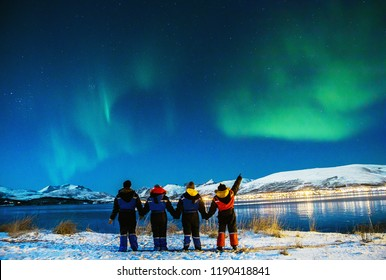 Group Tourists visiting in Tromso. Amazing beautiful Aurora, also know as Northern Lights dancing over the night sky. Travel, tourism, holidays concept.