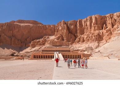 Group of tourists walk to famous mortuary temple of Hatshepsut. UNESCO World Heritage Site. Deir el-Bahari, Egypt.