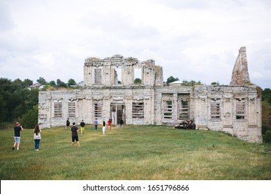 Group of tourists walking to old ruins of Skala Podilskyi castle, Ukraine. Destroyed ruined stone walls of medieval castle and green grass, historical palace in Europe - Shutterstock ID 1651796866