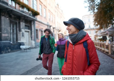 group of tourists walking on the streets of Lviv. Happy smiling woman with friends tourists in warm outdoor wear walking outdoors at autumn or spring day