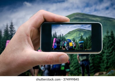 group of tourists watching the mountain to be the hard way. tourist photo, a man photographed tourist on a smartphone, phone in hand. tourists climb up the mountain, selfie phone