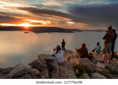 A group of tourists watching the sun set over islands on Lake Titicaca in Peru