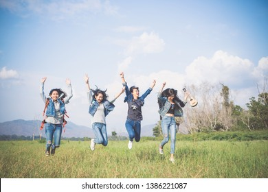 A group of tourists who jump happily among the grasslands.