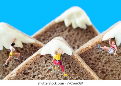 A group of toy mountaineers on mountains, made of rye bread and creamy cheese. Ecotourism and healthy eating concept.