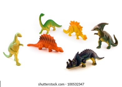 Group of toy plastic dinosaurs over white