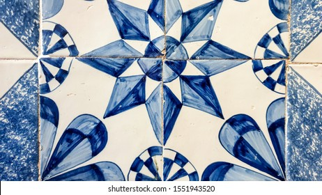 A group of traditional Dutch antique Delftware or Delft blue wall tiles, decorated with a star, abstract design.