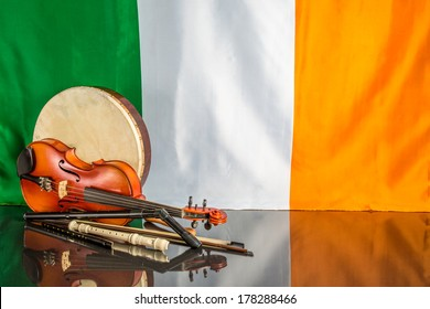 A group of traditional Irish musical instruments on a black table and Irish flag back ground