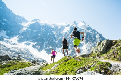A group of trail runners running along a high mountain trail under a blue summer sky in the Alps