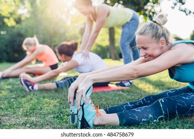 Group with trainer stretching workout on a green grass in the park