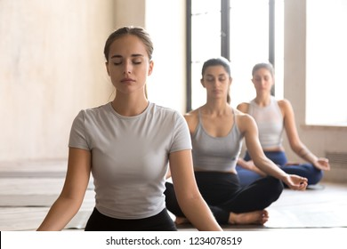 Group training of deep meditation at yoga studio class. Diverse young females sitting with closed eyes in lotus position meditate and visualizing together, feeling self-awareness serenity and calmness