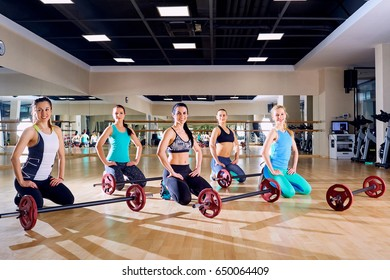 Group training. Girls sitting on  floor with a barbell in the gy