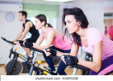 Group training people biking in the gym, exercising legs doing cardio workout cycling bikes.