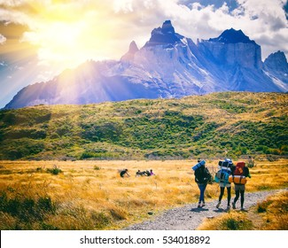 Group of travelers with backpacks walk along a trail towards a mountain ridge.Backpackers style. Concept of active leisure