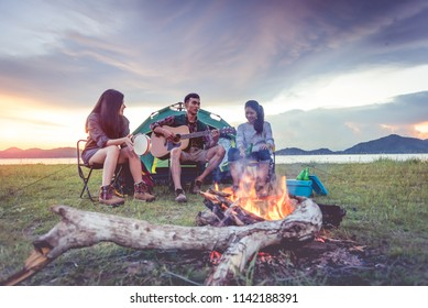 Group of travelers camping and doing picnic and playing music together. Mountain and lake background. People and lifestyle. Outdoors activity and leisure theme. Backpacker and Hiker. Dawn and twilight