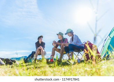 Group of travelers camping and doing picnic in meadow field foreground. Mountain and lake background. People and lifestyles concept. Outdoors activity and leisure theme. Backpacker and Hiker lifestyle