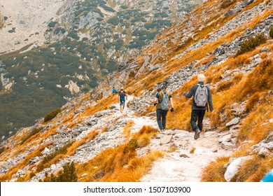 Group of travelers hiking down the mountainside, beautiful autumn mountain landscape