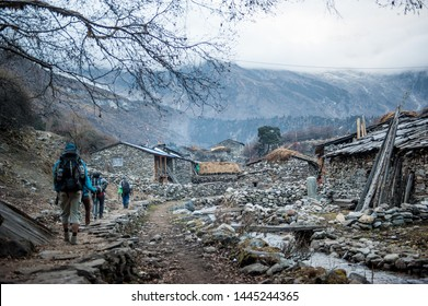 A group of trekkers heading to Samagau village on Manaslu circuit with view of Mount Manaslu range (8 156 meters). Himalayas, stone buildings in village, at Manaslu Glacier in Gorkha District in Nepal