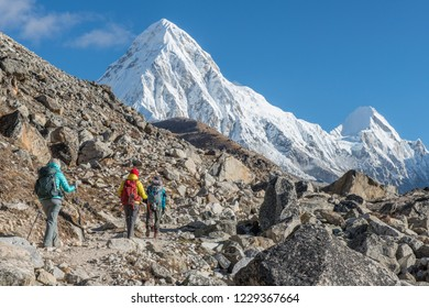 Group of trekkers trekking to Everest base camp in Sagarmatha National Park of Nepal with view of Mt.Pumori (7,161 m) and Lingtren (6,749 m) in the background.