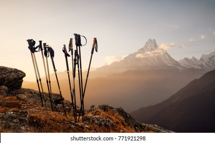 Group of trekking sticks on a mountain top background.