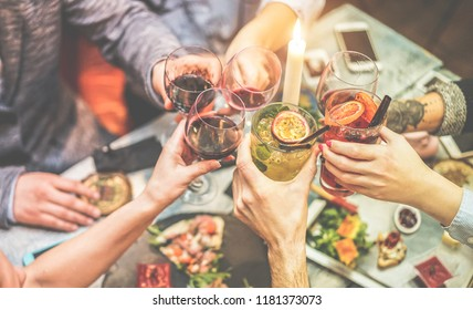 Group of trendy friends enjoying appetizer in american bar - Young people hands cheering with wine and tropical fruits cocktails - Radial purple and green filters editing - Focus on right hand glass