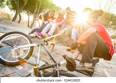 Group of trendy friends having fun together out at skate bmx park  - Youth friendship  concept with young people outdoors - Focus on afroamerican with stereo - Retro vibrant filter with sunflare halos