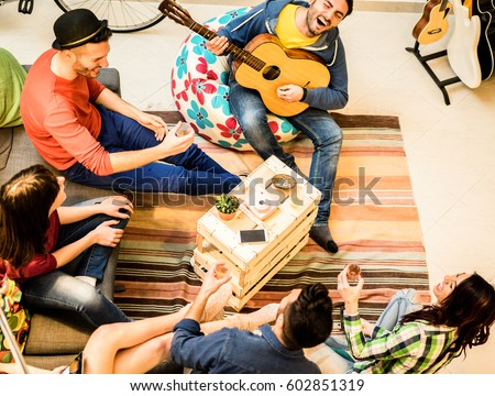 Group of trendy friends having fun in hostel living room - Happy young backpackers enjoying time together playing music with guitar and drinking beer - Focus on musician and wood table - Warm filter