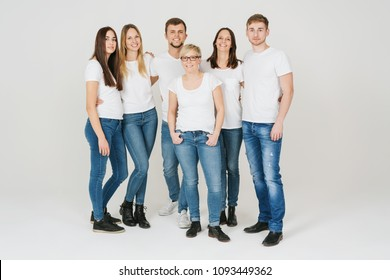Group of trendy relaxed friends in jeans and white t-shirts posing together over a white studio background smiling at the camera