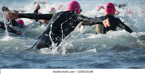 Group triathlon participants running into the water for swim portion of race,splash of water and athletes running