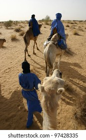 a group of Tuareg nomads rides their camels through the Sahara desert of Mali, Africa