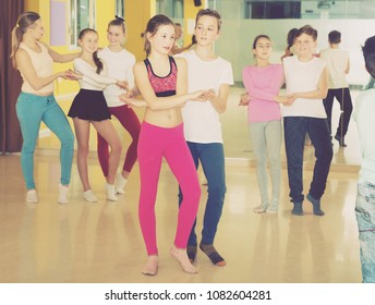 Group of tweens practicing vigorous jive movements in dance studio with female coach