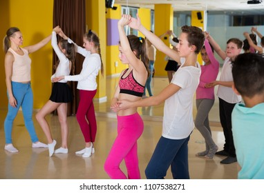 Group of tweens practicing vigorous jive movements in choreography class with woman coach