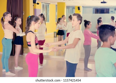 Group of tweens practicing vigorous jive movements in dance studio with woman coach