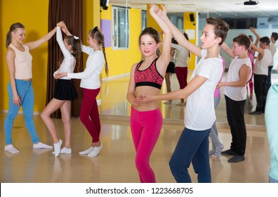 Group of tweens practicing vigorous jive movements in choreography class with female trainer