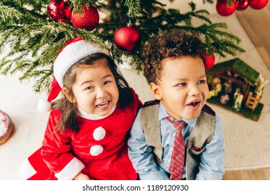 Group of two adorable 3 year old kids playing by the Christmas tree, top view