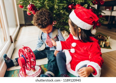 Group of two adorable 3 year old kids playing by the Christmas tree. Little girl admiring boy's tie