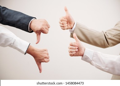 Group of two business partners showing thumb up and other two partners showing failure in business isolated on white background