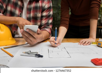 Group of two coworkers working with blueprint in office. co-working teamwork concept.
