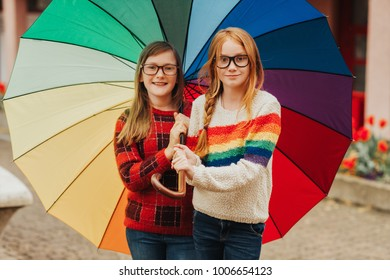 Group of two cute little girls playing outside under big colorful umbrella, wearing glasses and warm pullovers