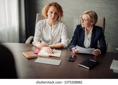 Group of two female corporate mentors check the knowledge of the woman trainee at the end of the trial period