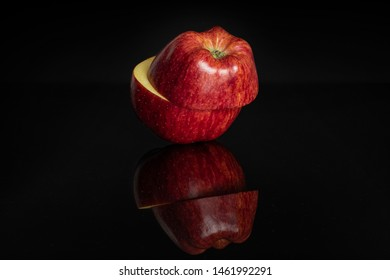 Group of two halves of fresh apple red delicious one on top of the other isolated on black glass