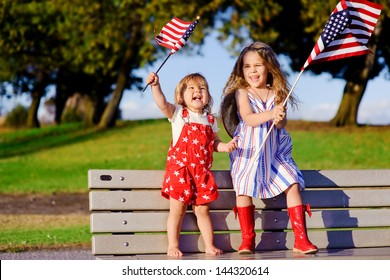 group of two happy adorable little kid girls smiling and waving American flag outside, his dress with strip and stars, cowboy hat. Smiling child celebrating 4th july - Independence Day